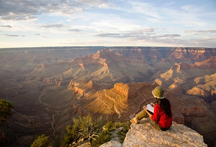 Woman Writing in Journal at Rim of Grand Canyon at Sunset